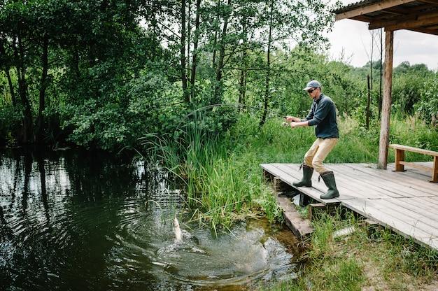 Dobry chwyt ryba trofeum. rybak z wędką złapał dużego szczupaka rybnego z wody na molo.