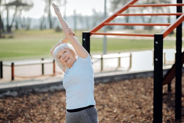 Dobry dzień. zadowolona szczupła kobieta uśmiechnięta i ćwicząca na świeżym powietrzu