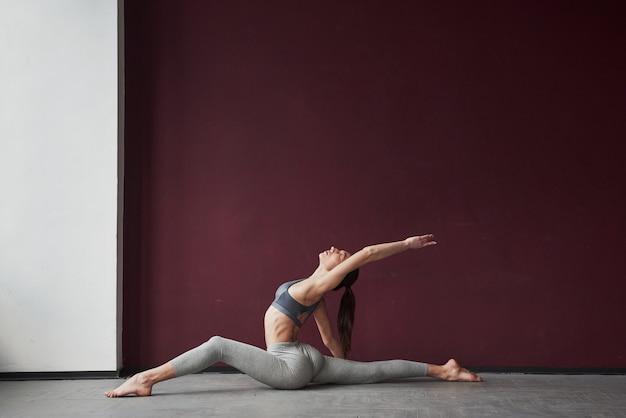 Dobry film. dziewczyna z dobrą sylwetką fitness ma ćwiczenia w przestronnym pokoju