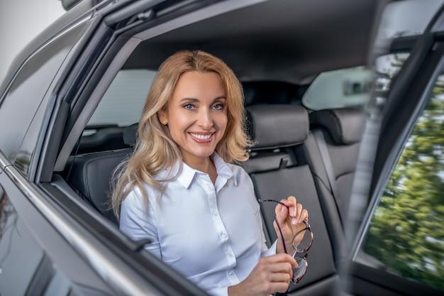 Dobry humor. blondynka siedzi w samochodzie i uśmiecha się
