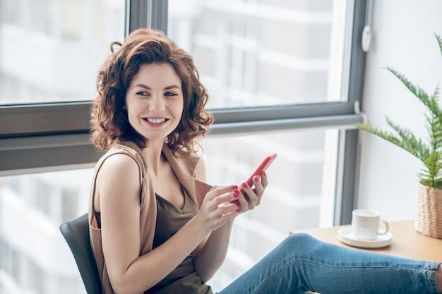 Dobry humor. ciemnowłosa kobieta siedzi z telefonem w ręce i uśmiecha się