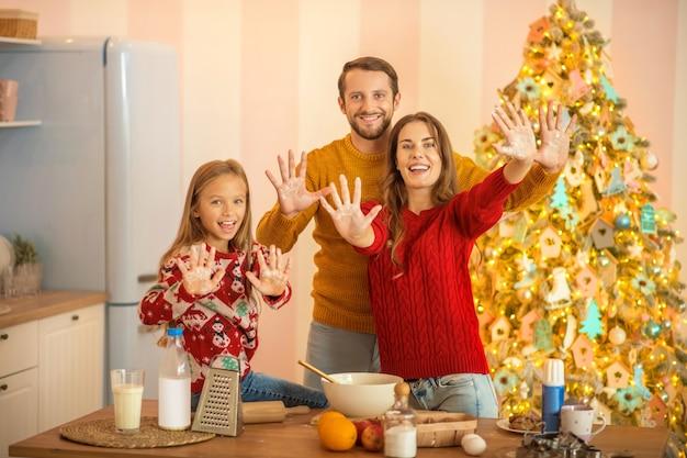 Dobry humor. dziecko i jej rodzice gotują razem w kuchni i czują się świetnie