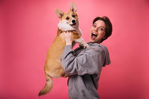Dobry humor kobieta trzyma psa i śmiejąc się na różowym tle. emocjonalna sierściowłosa dziewczyna w szarej bluzie z kapturem pozuje z corgi na na białym tle