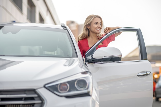Dobry humor. ładna kobieta w czerwonej sukience patrząc szczęśliwy, stojąc w pobliżu samochodu