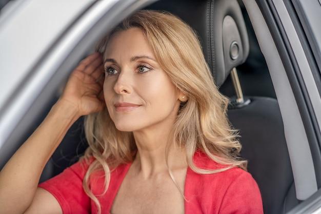 Dobry humor. ładna kobieta w czerwonej sukience siedzi w samochodzie i wygląda pozytywnie