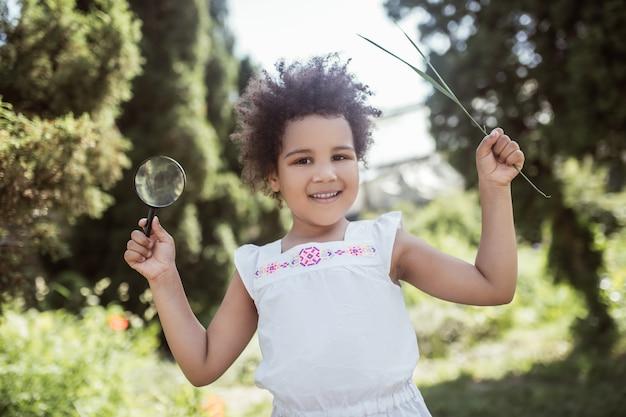 Dobry humor. mała dziewczynka z kręconymi włosami trzyma lupę i wygląda wesoło