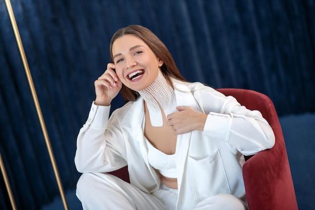 Dobry humor. młoda kobieta z taśmami na szyi siedzi na krześle i patrzy wesoło