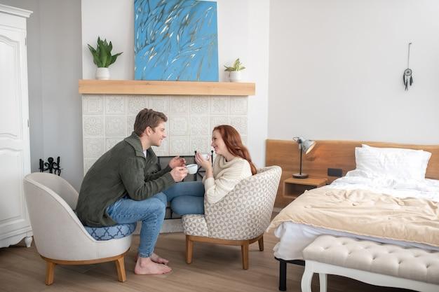 Dobry humor. młoda szczęśliwa imbirowa kobieta i uważny mężczyzna pijący kawę komunikujący się w fotelach przy kominku