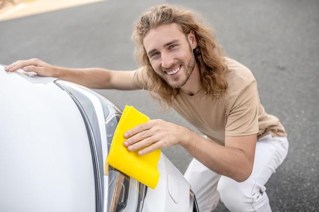 Dobry humor. młody człowiek maszyna do czyszczenia reflektorów samochodowych i uśmiechnięty
