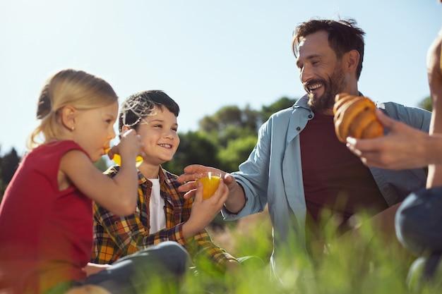Dobry humor. radosny ciemnowłosy chłopak uśmiecha się i pije sok podczas pikniku