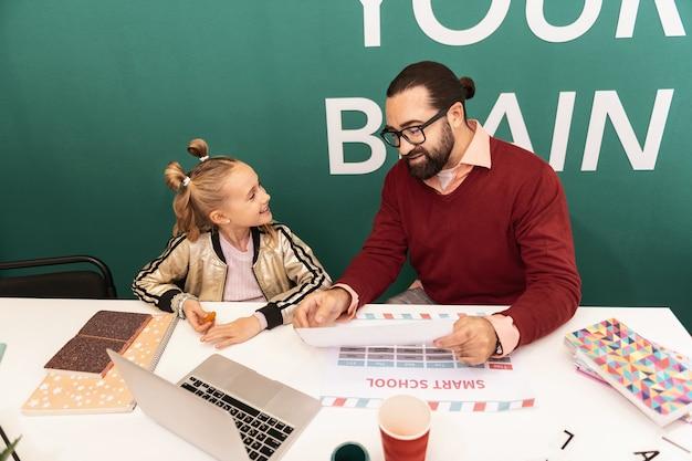 Dobry humor. śliczna jasnowłosa dziewczyna nosi bransoletki na dłoni, uśmiechając się do swojego nauczyciela