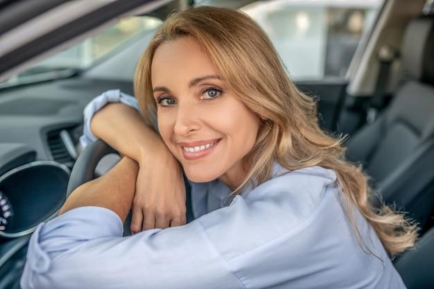 Dobry humor. uśmiechnięta blondynka siedzi w samochodzie i wygląda na zadowoloną