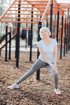 Dobry humor. zadowolona blond kobieta uśmiechając się i ćwicząc na świeżym powietrzu