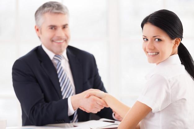 Dobry interes. dwie osoby w stroju formalnym podają sobie ręce i patrzą w kamerę siedząc przy stole