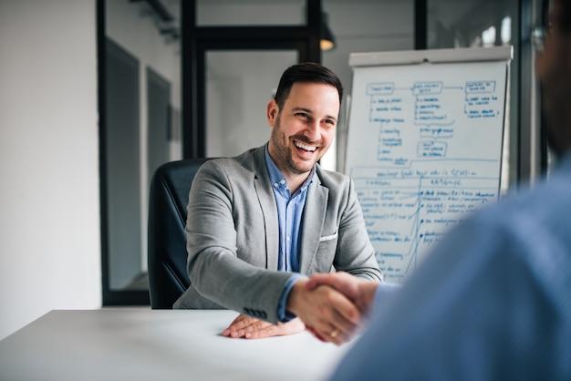 Dobry interes. dwóch ludzi biznesu drżenie rąk siedząc w miejscu pracy.