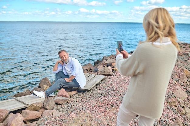 Dobry kąt. kobieta w lekkich, casualowych ubraniach, stojąca tyłem do aparatu, robiąca zdjęcia poważnego pozującego mężczyzny siedzącego na ziemi w pobliżu wody