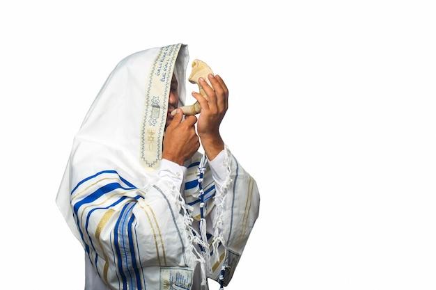 """Dobry na białym tle: żyd rabin w tałesie z napisem po hebrajsku """"baruch atah adonai"""", dmuchający w szofar, barani róg rosz haszana (nowy rok). prawosławny"""