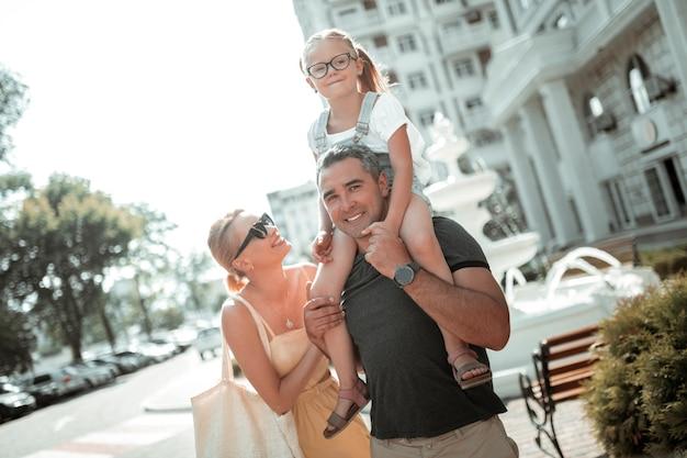Dobry nastrój. wesoła dziewczynka jedzie na jej uśmiechniętych ojców ramionach z matką stojącą za nią.
