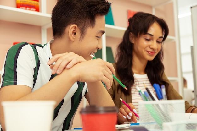 Dobry nastrój. wesoły student zagraniczny zachowujący uśmiech na twarzy podczas ćwiczenia umiejętności językowych