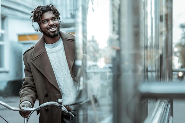 Dobry nastrój. zadowolony międzynarodowy mężczyzna z uśmiechem na twarzy podczas słuchania muzyki