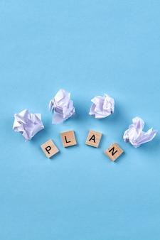 Dobry plan na sukces. drewniane kostki z literami. zmięty papier na białym tle na niebieskim tle.
