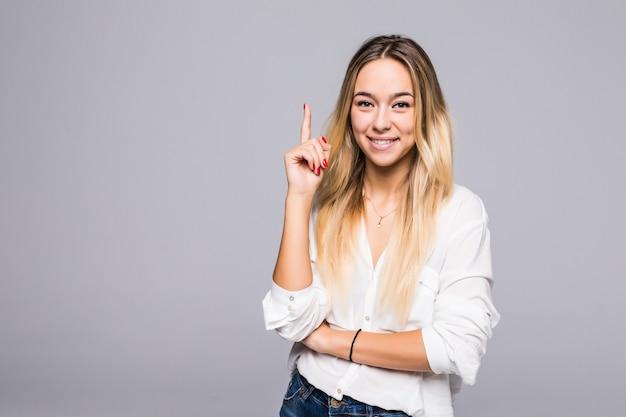 Dobry pomysł. pomyślna uśmiechnięta kobieta na szarej ścianie wskazuje palcami w górę.