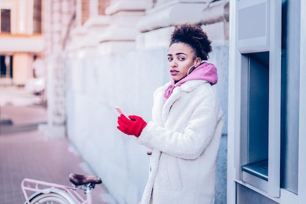 Dobry pomysł. skoncentrowana dziewczyna trzymając telefon w obu rękach, patrząc na kamery