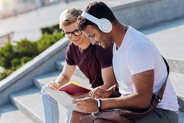 Dobry pomysł. uważny, brodaty mężczyzna siedzi obok swojego kolegi z grupy i wyraża pozytywne nastawienie, patrząc na laptopa