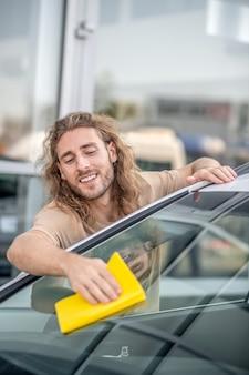 Dobry samochód. młody człowiek-maszyna do czyszczenia samochodu i wyglądający na zadowolonego
