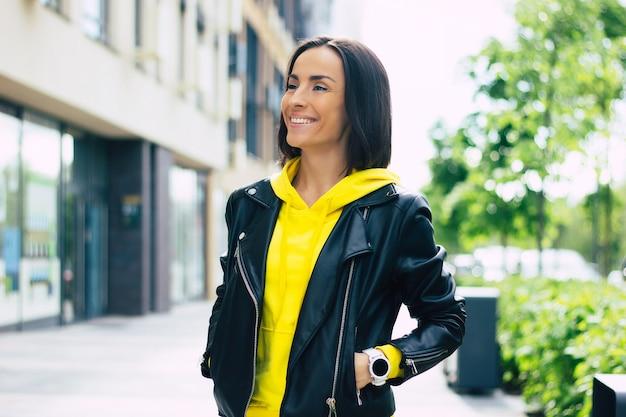 Dobry spacer z moim smartwatchem! młoda kobieta ubrana w skórzaną kurtkę i żółtą bluzę z kapturem, ciesząca się spacerem ze swoim nowym smartwatchem.