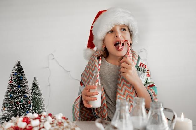 Dobry świąteczny poranek blond chłopiec w czerwonej czapce mikołaja pije mleko i liże słodką trzcinę cukrową