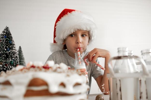 Dobry świąteczny poranek. blond chłopiec w czerwonym kapeluszu santa ma śniadanie, pije mleko.