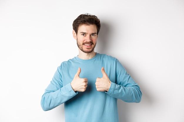 Dobry wybór. atrakcyjny kaukaski mężczyzna z brodą pokazujący kciuki do góry i uśmiechnięty, lubiący i aprobujący dobry produkt, polecający coś, stojący na białym tle