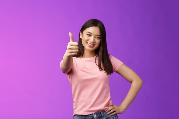 Dobry wybór, dobra robota. zadowolona szczęśliwa azjatka w różowym t-shircie pokazuje kciuk w górę, aprobuje swój pomysł, uśmiecha się radośnie, akceptuje plan, zgadza się, poleca produkt, wydaje pozytywną ocenę.