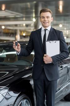 Dobry wybór! przystojny młody sprzedawca klasycznych samochodów stojący w salonie i trzymający klucz