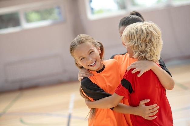 Dobry wynik. dzieci w jasnych strojach sportowych przytulają się i czują się szczęśliwe