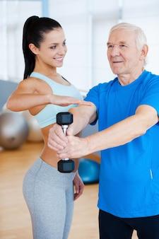 Dobrze ci idzie! pewna siebie fizjoterapeutka pomaga starszemu mężczyźnie w fitness w klubie fitness