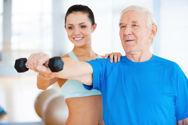Dobrze ci idzie! wesoła fizjoterapeutka pomaga starszemu mężczyźnie w fitness w klubie fitness