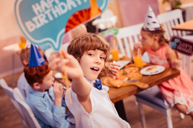 Dobrze dla ciebie. słodkie dziecko wyrażające pozytywne nastawienie będąc na przyjęciu urodzinowym