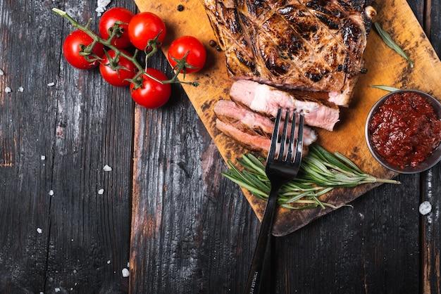Dobrze grillowany stek wołowy marynowany na drewnianej desce, na stole świeże warzywa. wolne miejsce na tekst