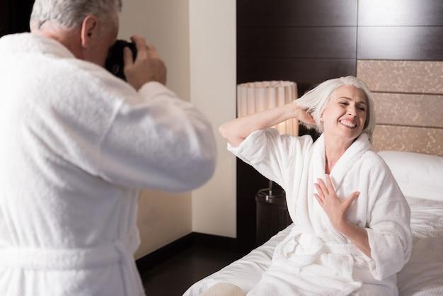 Dobrze się bawimy. uśmiechnięta, rozbawiona starsza kobieta siedzi na łóżku i pozuje do swojego mężczyzny, wyrażając radość i zabawę