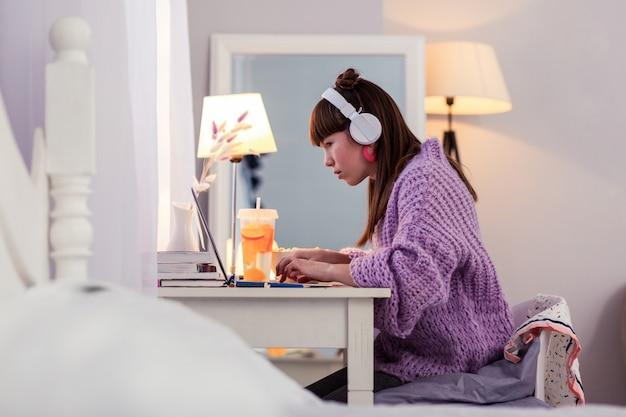 Dobrze się uczyć. poważny uczeń noszący słuchawki podczas oglądania wideo