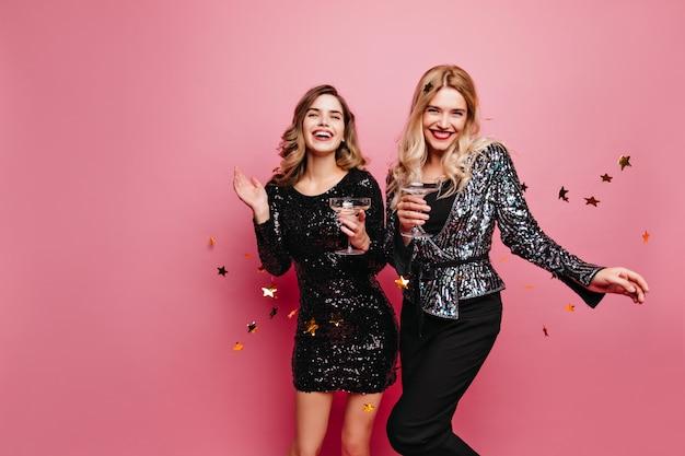 Dobrze ubrana blondynka trzyma kieliszek do wina, pozując pod konfetti. wewnątrz zdjęcie wesołych dziewcząt rasy kaukaskiej świętujących święta szampanem.