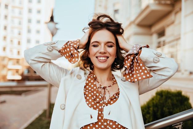 Dobrze ubrana brunetka dziewczyna ze stylowym makepem spacerującym po mieście. zewnątrz portret błogiej modelki z falistą fryzurą.