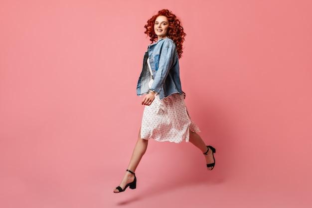 Dobrze ubrana dziewczyna w butach na wysokim obcasie skacząca na różowym tle. pełny widok długości młodej kobiety w dżinsowej kurtce.