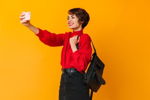 Dobrze ubrana kobieta z plecakiem przy selfie