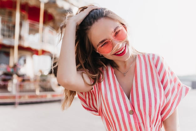 Dobrze ubrana śliczna dziewczyna dotyka jej włosów, pozując w pobliżu karuzeli. biała błoga kobieta w okularach przeciwsłonecznych spędza weekend w letnim parku rozrywki.
