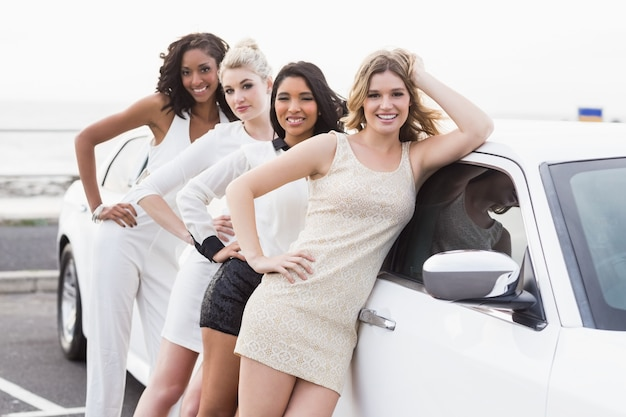 Dobrze ubrane kobiety pozujące, opierając się na limuzynie