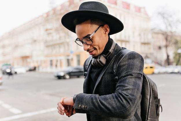 Dobrze ubrany afrykański dżentelmen spoglądający na zegarek. plenerowe zdjęcie mulata w kapeluszu nosi skórzany plecak.