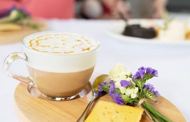 Dobrze udekorowany kubek gorącej kawy podawany na danie drewniane i mały fioletowy kwiat i herbatniki